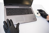 Burglar hacking and putting a cd-rom in laptop