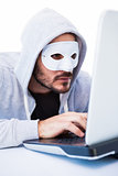 Man wearing mask while hacking into laptop