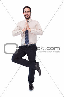 Smiling businessman standing in tree pose