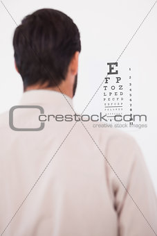 Focused man in suit on eye test letters