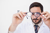 Doctor wearing lab coat looking through eyeglasses