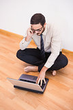 Businessman sitting on floor using mobile phone and laptop