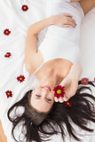 Pretty brunette posing in bed with flowers