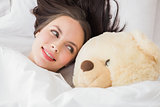 Pretty brunette under the duvet with teddy bear