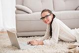 Pretty brunette using laptop on the floor