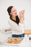 Pretty brunette eating slice of pizza