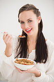 Pretty brunette eating bowl of cereal