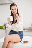 Pretty brunette holding a mug and cookie