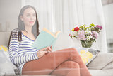 Pretty brunette reading book on couch