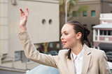 Young businesswoman hailing a cab