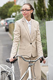 Young businesswoman standing with bike