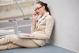 Young businesswoman using laptop on the phone