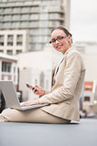 Young businesswoman using laptop holding her phone