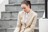 Young businesswoman sitting on steps