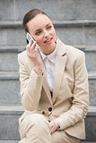 Young businesswoman sitting on steps on the phone