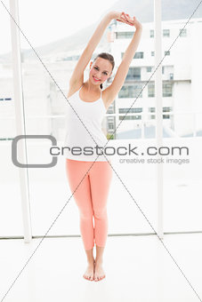 Fit brunette stretching and smiling