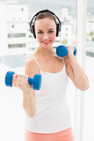 Fit brunette holding blue dumbbells