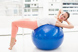 Fit brunette stretching on an exercise ball