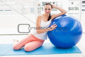 Fit brunette sitting beside exercise ball
