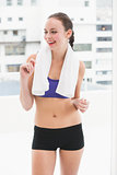 Fit brunette smiling with towel on shoulders