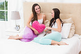Pretty friends chatting on bed