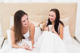 Pretty friends having coffee in bed