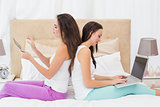 Pretty friends using their technology on bed