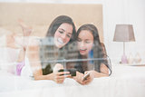 Pretty friends looking at smartphone on bed