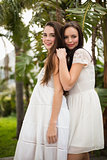 Pretty friends smiling in white dresses
