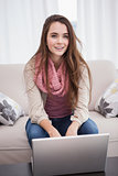 Pretty brunette using laptop on the couch