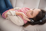 Pretty brunette listening to music on the couch