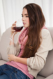 Pretty brunette drinking wine on couch