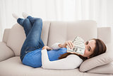 Pretty brunette showing cash on couch