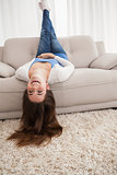 Pretty brunette lying upside down on couch