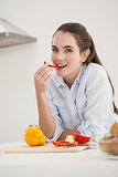 Pretty brunette eating sliced pepper