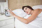 Pretty brunette turning off her alarm