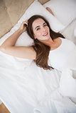 Pretty brunette lying in bed smiling at camera