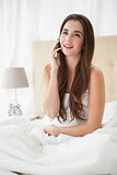 Pretty brunette talking on the phone in bed