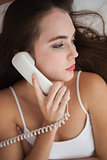 Pretty brunette on the phone in bed