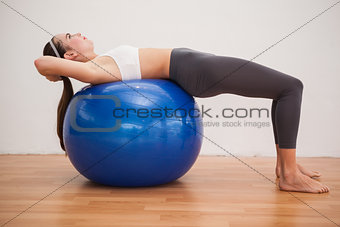 Fit brunette working out with exercise ball