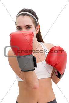 Fit brunette in boxing gloves