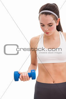 Fit brunette holding blue dumbbell