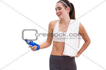 Fit brunette looking at sports bottle