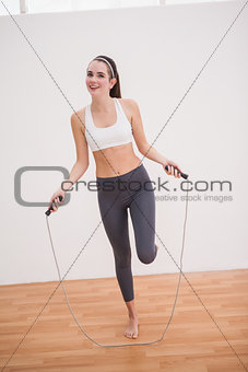Fit brunette using skipping rope