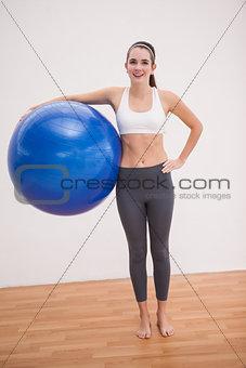Fit brunette holding exercise ball