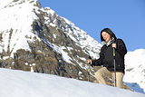 Happy hiker woman trekking on the snow in the mountain
