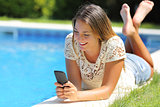 Teenager girl using a smart phone resting on a pool side