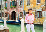 Portrait of smiling young woman in venice, italy looking at map