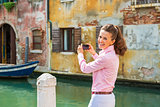 Happy young woman in venice, italy taking photo