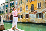 Full length portrait of happy young woman taking photo in venice
